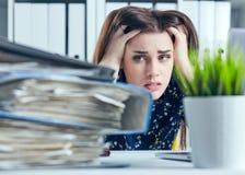 Den trötta och utmattade kvinnan ser berget av dokument som upp propping hennes huvud med henne händer arkivbilder