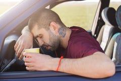 Den trötta orakade mannen lutar på hjulet, och håll skyler över brister koppen kaffe, har sömnigt uttryck, sitter i bil, slumrar  arkivfoton