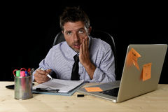 Den trötta spänningen för affärsmanlidandearbete slöde bort bekymrat upptaget i regeringsställning sent på natten med bärbar dato arkivbilder