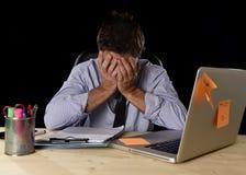 Den trötta spänningen för affärsmanlidandearbete slöde bort bekymrat upptaget i regeringsställning sent på natten med bärbar dato royaltyfria foton