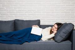 Den trötta unga kvinnan som tar en ta sig en tupplur hemmastatt ligga på en soffa med en bok som ligger över hennes bröstkorg och fotografering för bildbyråer