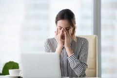 Den tröttade affärskvinnan som masserar ögonkänsla för att anstränga trötthetshuvudvärken som avlöser, smärtar arkivfoton