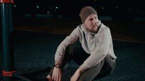 Den tröttade idrottsmannen vilar, efter utbilda in parkera på natten som sitter på jordning stock video