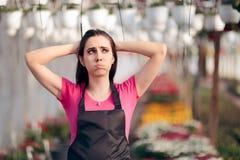 Den tröttade kvinnliga arbetaren i blom- växthuskänsla förkrossade royaltyfria foton