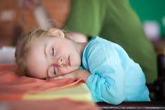 Den tröttade lilla flickan och faller sovande i kafé Royaltyfria Bilder
