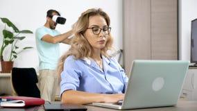 Den tröttade och streesed kvinnan arbetar på datoren, medan hennes pojkvän bär virtuell verklighethörlurar med mikrofon i bakgrun arkivfilmer