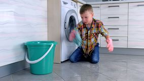 Den tröttade pojken i gummihandskar önskar inte att tvätta golvet i köket Sätter av handskar och kastar den på golvet arkivfilmer