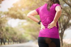 Den tröttade unga asiatiska sportflickan känner sig smärtar på henne baksida och höften, medan öva, hälsovårdbegreppet arkivbilder