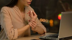 Den tröttade unga damen som skriver på bärbar datorkänsla, smärtar, i handled och gnidning den, stopptid lager videofilmer