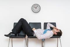 Den tröttade uttråkade mannen sover i väntande rum på stolar royaltyfria foton