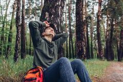 Den tr?ttade manturisten som sover i v?rskoghandelsresande, stoppade f?r att ha att vila campa, resande- och sportbegrepp fotografering för bildbyråer