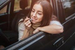 Den Tractive kvinnan applicerar rosa läppstift framme av backspegeln i bil tät hand upp isolerad white för höst begrepp höstlig s royaltyfri bild