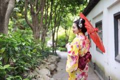 Den traditionella asiatiska japanska härliga brudGeishakvinnan bär kimonohållen ett vitt rött paraply i en sommarnaturträdgård Fotografering för Bildbyråer