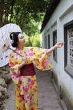 Den traditionella asiatiska japanska härliga brudGeishakvinnan bär kimonohållen ett vitt rött paraply i en sommarnaturträdgård Royaltyfri Fotografi