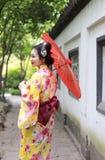 Den traditionella asiatiska japanska härliga brudGeishakvinnan bär kimonohållen ett vitt rött paraply i en sommarnaturträdgård Arkivfoton