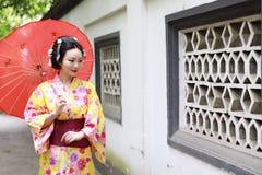 Den traditionella asiatiska japanska härliga Geishabrudkvinnan bär kimonohållen ett paraply i en sommarnaturträdgård Royaltyfria Bilder