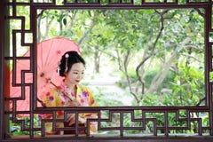 Den traditionella asiatiska japanska härliga Geishakvinnabruden bär kimonot med det röda paraplyet förestående i en sommarnatur Arkivfoton