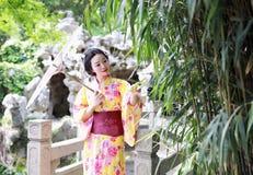 Den traditionella asiatiska japanska härliga Geishakvinnan bär det röda vita paraplyet för kimonohållen vid bambu i en trädgård f Arkivbild