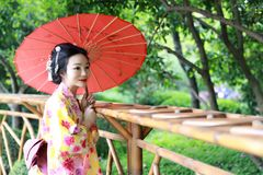 Den traditionella asiatiska japanska härliga Geishakvinnan bär kimonobruden med ett rött paraply i en graden Royaltyfria Foton