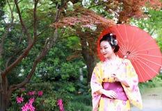 Den traditionella asiatiska japanska härliga Geishakvinnan bär kimonohållen ett paraply förestående i en sommarnatur Royaltyfri Fotografi