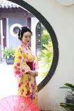 Den traditionella asiatiska japanska härliga Geishakvinnan bär kimonohållen ett paraply förestående i en sommarnatur Arkivfoton