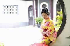 Den traditionella asiatiska japanska härliga Geishakvinnan bär kimonohållen ett paraply förestående i en sommarnatur Arkivfoto