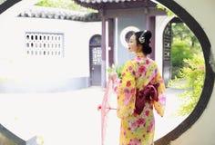 Den traditionella asiatiska japanska härliga Geishakvinnan bär kimonohållen ett paraply förestående i en sommarnatur Arkivbild