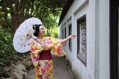 Den traditionella asiatiska japanska härliga Geishakvinnan bär kimonohållen ett vitt rött paraply i en sommarnaturträdgård Arkivbilder