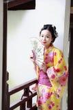 Den traditionella asiatiska japanska härliga Geishakvinnan bär kimonohållen som en fan sitter i en sommarnaturträdgård Royaltyfri Foto