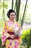Den traditionella asiatiska japanska härliga Geishakvinnan bär kimonohållen som en fan under ett träd i en sommar graden föreståe Royaltyfri Bild
