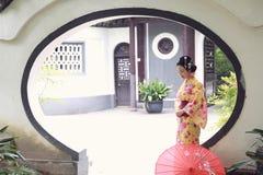 Den traditionella asiatiska japanska härliga Geishakvinnan bär kimonohållen som ett paraply i en sommar graden förestående Royaltyfri Bild