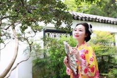 Den traditionella asiatiska japanska härliga Geishakvinnan bär kimonoläseboken i en sommarnatur Royaltyfria Bilder