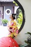 Den traditionella asiatiska japanska härliga Geishakvinnan bär kimonoläseboken i en sommarnatur Arkivbild