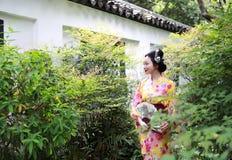 Den traditionella asiatiska japanska härliga Geishakvinnan bär kimonot med en fan förestående i en sommarnatur Royaltyfria Foton
