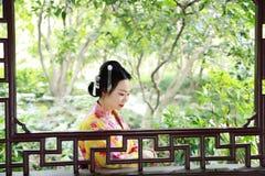 Den traditionella asiatiska japanska härliga Geishakvinnan bär kimonot med en fan förestående i en sommarnatur Arkivfoton