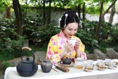 Den traditionella asiatiska japanska härliga Geishakvinnan bär te för drink för ceremoni för konst för kimonoshowte i en trädgård Royaltyfri Foto