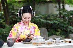 Den traditionella asiatiska japanska härliga Geishakvinnan bär te för drink för ceremoni för konst för kimonoshowte i en trädgård Arkivfoton