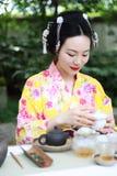 Den traditionella asiatiska japanska härliga Geishakvinnan bär te för drink för ceremoni för konst för kimonoshowte i en trädgård Arkivfoto