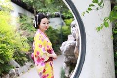 Den traditionella asiatiska japanska härliga kvinnabruden bär kimonoställningen i utomhus- vårträdgård Royaltyfri Foto