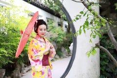 Den traditionella asiatiska japanska härliga kvinnabruden bär kimonot med det röda paraplyet i utomhus- vårträdgård Royaltyfri Foto