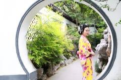 Den traditionella asiatiska japanska härliga kvinnabruden bär kimonot med det röda paraplyet i utomhus- vårträdgård Royaltyfria Foton