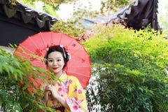 Den traditionella asiatiska japanska härliga kvinnabruden bär kimonot med det röda paraplyet som är främst av en tempel i utomhus Fotografering för Bildbyråer