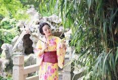 Den traditionella asiatiska japanska härliga kvinnabruden bär kimonot med den vita paraplyställningen vid bambu i utomhus- vårträ Arkivfoton