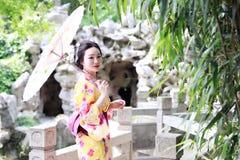 Den traditionella asiatiska japanska härliga kvinnabruden bär kimonot med den vita paraplyställningen vid bambu i utomhus- vårträ Royaltyfri Fotografi
