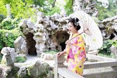 Den traditionella asiatiska japanska härliga kvinnabruden bär kimonot med den vita paraplyställningen vid bambu i utomhus- vårträ Arkivbilder