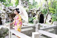 Den traditionella asiatiska japanska härliga kvinnabruden bär kimonot med den vita paraplyställningen vid bambu i utomhus- vårträ Fotografering för Bildbyråer