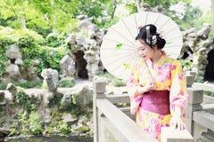 Den traditionella asiatiska japanska härliga kvinnabruden bär kimonot med den vita paraplyställningen vid bambu i utomhus- vårträ Arkivfoto