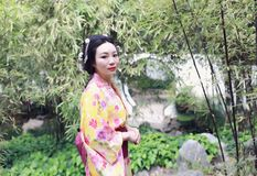 Den traditionella asiatiska japanska härliga kvinnan bär kimonot i en vårträdgård parkerar ställningen vid bambu tycker om fri ti Arkivfoto