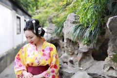 Den traditionella asiatiska japanska härliga kvinnan bär kimonot i en vårträdgård parkerar ställningen vid bambu tycker om fri ti Royaltyfri Fotografi
