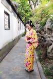 Den traditionella asiatiska japanska härliga kvinnan bär kimonot i en vårträdgård parkerar ställningen vid bambu tycker om fri ti Fotografering för Bildbyråer